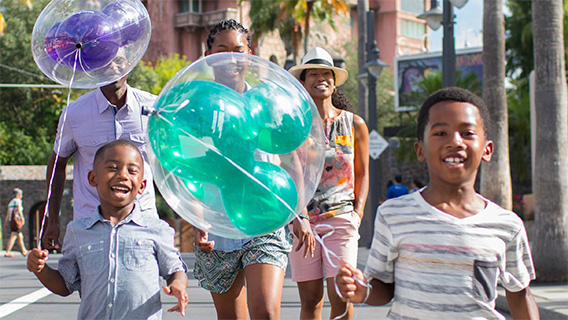 Young guests with Mickey balloons on Sunset Boulevard at Disney's Hollywood Studios
